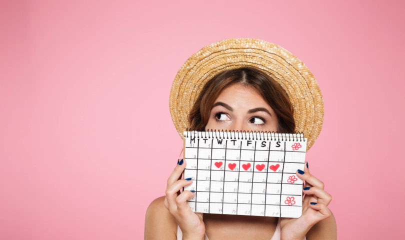 a girl with a straw hat holding a calendar